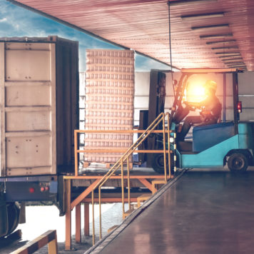 Forklift handling empty cans from container into warehouse. Distribution, Logistics Import Export, Warehouse operation, Trading, Shipment, Delivery concept.